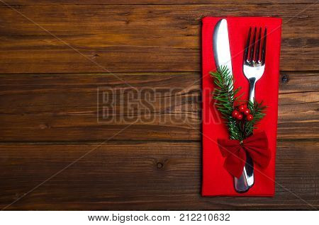 Christmas Table: Knife And Fork, Napkin And Christmas Tree Branch On A Wooden Table Top View With Co