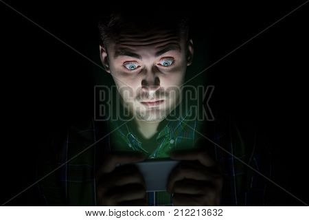 The Guy In The Shirt Sits In The Dark And Looks At The Mobile Phone. His Face Has Emotions Of Surpri
