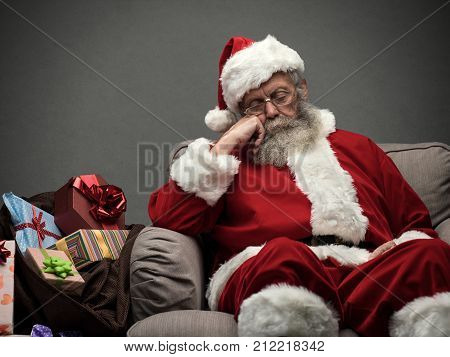 Sleepy Santa Claus taking a nap and relaxing on the armchair on Christmas Eve poster