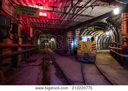Underground emerald ore mine shaft tunnel gallery passage with light electric locomotive poster