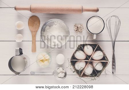 Baking background. Top view of cooking ingredients and utensils for yeast dough on white rustic wood. Making pastry flat lay.