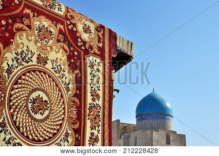 2013 November 11, handmade carpet as a a symbol of wealth against ancient mosque with blue dome and brick wall Bukhara Uzbekistan