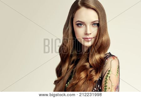 Brunette  girl with long  and   shiny curly hair .  Beautiful  model woman  with wavy hairstyle. Care and beauty of hair products .
