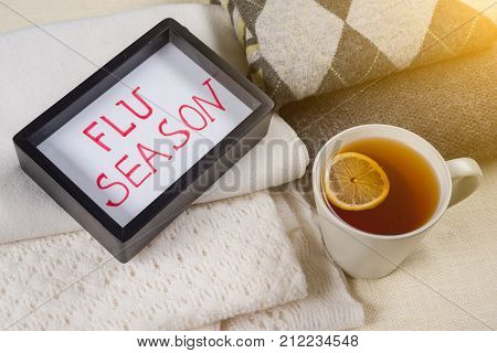 Flu season - text in frame. Background - warm woolen clothes, a cup of hot tea.