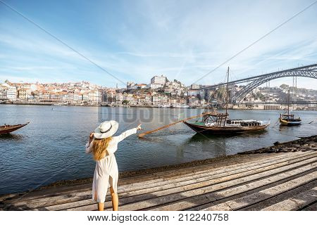 Young woman traveler enjoying beautiful cityscape view Douro river and traditional portuguese boats during the morning light in Porto, Portugal