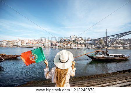 Young woman traveler standing back with portuguese flag, enjoying beautiful cityscape view on Douro river and boats during the morning light in Porto, Portugal