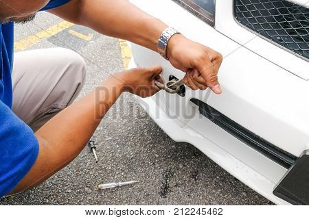 Mechanic Fixing Hook And Chain Onto Car To Tow