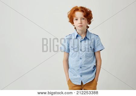 Beautiful little boy with ginger hair and freckles holding hands in pockets looking in camera having serious but unconfident look