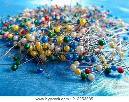 pile of of multi-colored sewing pins on a blue background