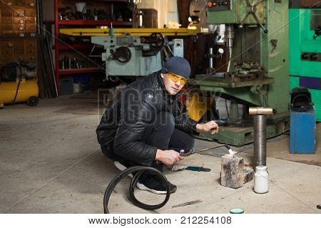 Work man is a welder in mask, metal product at home garage, with flame burning gas welding