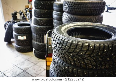New winter tires in stacks inside automotive garage service - changing wheels or tires concept