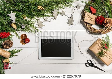 Juniper branches with a Christmas decor. Christmas, New Year background. Coniferous branches of juniper and white tablet with black screen. Top view, flat design. Christmas tree on white wooden background.