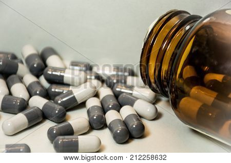 open pill bottle spilled pills and abstract angle black and white big pharma suicide rate opioid epidemic
