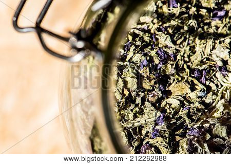 glass jar full of mallow leaves and flowers for healthy infusion mallow tea