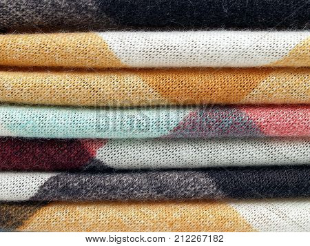 close-up pile of colorful woven fabric, pattern stripe of earth tone cloth abstract texture background