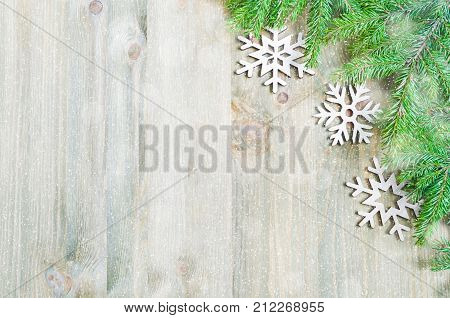 Christmas background. Christmas toys green fir tree on the wooden background. Christmas still life with free space for text. Festive Christmas background with wooden snowflakes. Christmas card