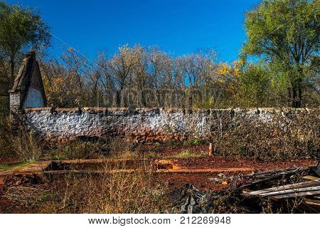 A wall of an old abandoned ruined brick house visible through thickets. The debris of an old building. A sunny day, autumn, Ukraine