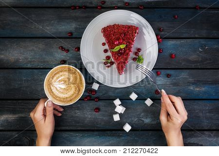 Top View. slice of sweet and delicious Red velvet cake and latte coffee with women's hands on a colored wooden background.