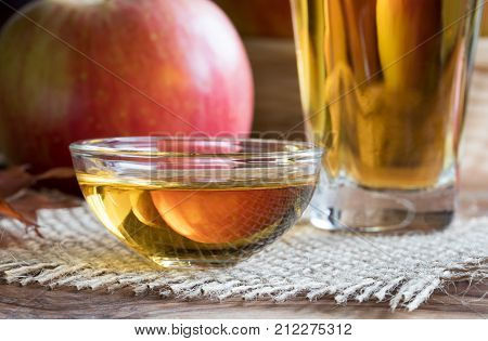 Apple Cider Vinegar In A Glass Bowl, With An Apple In The Background