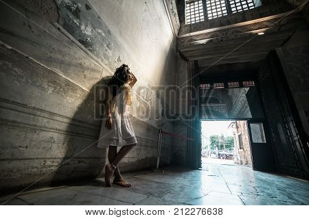 Believer girl stands in the temple in the rays of light and looks up in search of God