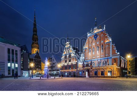House of Blackheads in the Town Hall Square and the spire of the Cathedral in the historic center of the old city against background of night sky. Riga, Latvia