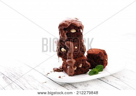 Cake chocolate brownies with dark chocolate dressing and mint on wooden table.