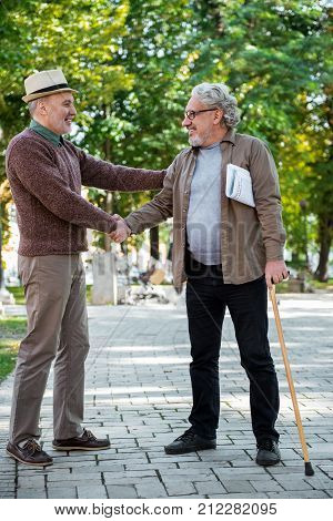 Full length portrait of joyful mature man greeting his old friend by handshake outdoor. He is carrying newspaper and walking stick. Comrades are talking and laughing