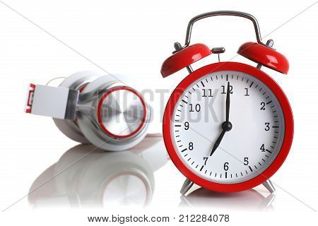 Red alarm clock with headphones isolated on white background shows seven minutes of the morning it's time to get up to wake up and have breakfast morning or evening jog to go to work music listen.