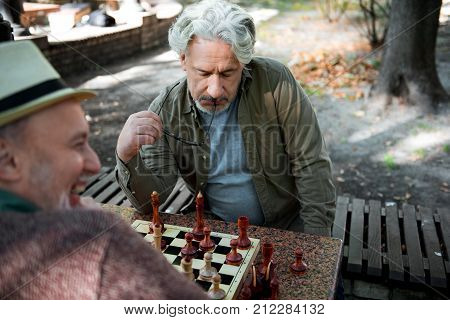 Difficult task. Portrait of puzzled senior man playing chess with smiling opponent. He is touching eyeglasses frame to his lips pensively while sitting outdoor