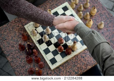 Top view close up of male arm of mature pensioner congratulating his opponent by handshake after checkmate