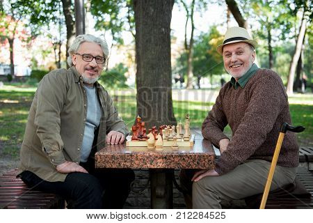 Spending free time with friend. Portrait of happy two senior men playing chess together in park. They are looking at camera and smiling