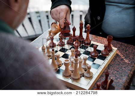 Top view close up of moving horse figurine forward on chessboard. His male opponent is sitting opposite