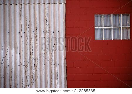 The close-up of a window made of glass tiles on a red-painted wall with adjoining corrugated iron.