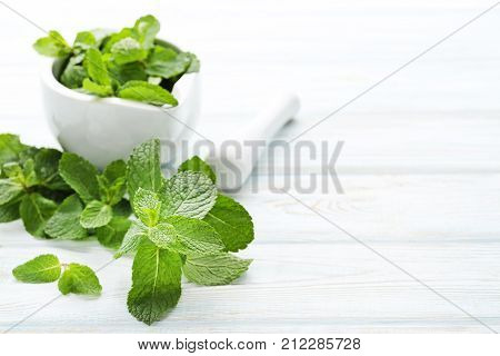 Fresh Mint Leafs In Mortar On White Wooden Table