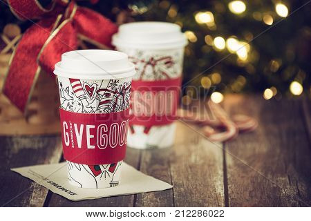 Dallas TX - November 4 2017: Starbucks popular holiday beverage served in the new 2017 designed holiday cups. Displayed with candy canes on wooden rustic table. Sparkling Christmas tree lights background.