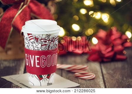 Dallas TX - November 4 2017: Starbucks popular holiday beverage served in the new 2017 designed holiday cup. Displayed with candy canes on wooden rustic table. Sparkling Christmas tree lights background.