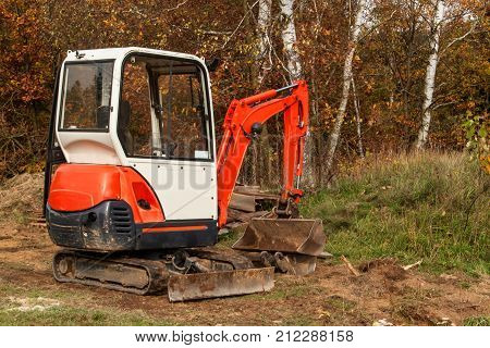 Mini excavator on a building site. Excavation work. The excavator works in the garden