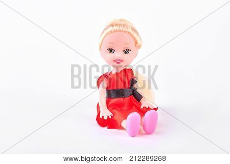 Beautiful baby doll on white background. Little doll with blond hair in red dress sitting over white background.