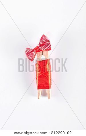Clothespin in red apparel, white background. Wooden clothes peg in red dress and bow isolated on white background. Creativity and art.