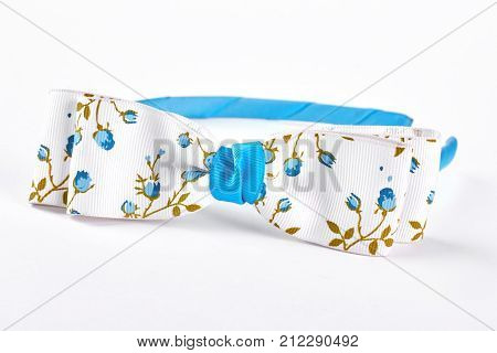 Beautiful blue head band with bow. Girls fashion hair band with bow isolated on white background. Little girls fashion accessory.