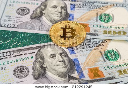 Golden bitcoin lying over american dollar bills and electronic circuit board. Business concept