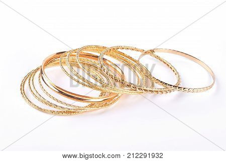 Gentle golden bracelets over white background. Collection of gold wrist bands isolated on white background.
