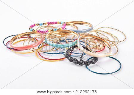 Many bracelets on white background. Collection of women fashion bangles. Female jewelry on white background.