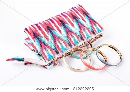 Make up bag and colorful bracelets. Fashion toiletry bag with modern bangles on white background close up. Woman fashion accessories.