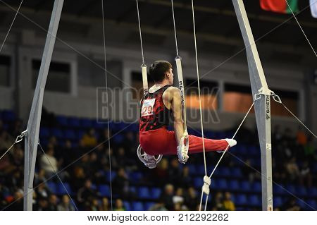 Male Gymnast Performing On Stationary Gymnastic Rings