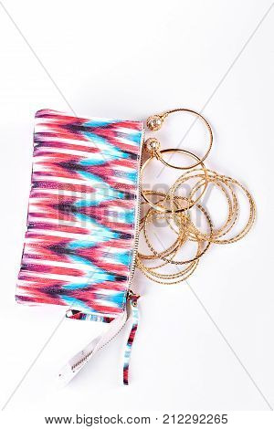 Open out cosmetics bag and bracelets. Stylish bag for toiletry and golden wrist bands, top view. Make up bag and jewelry.