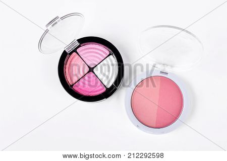 Three colors pink eyeshadows and blush. Two compact open boxes with eyeshadows and blush isolated on white background, top view.