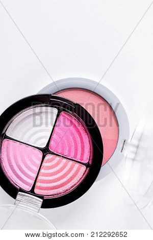 Pink tone eyeshadows and blush. Blusher powder and four colors pink eyeshadows in round plastic boxes on white background, top view.