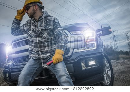 Contractor Worker Taking Break. Caucasian Electric Technician Seating on Front Bumper of His Pickup Truck. Remote Location.