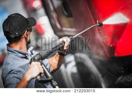 Truck Driver Washing His Semi Truck Tractor. Trucking Theme.